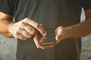 Photo of man dialing from a cell phone to report child abuse